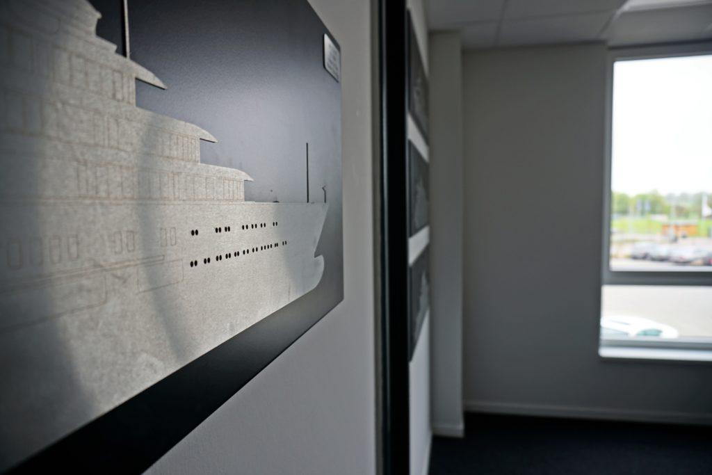 An der Wand im Besprechungsraum präsentieren sich die stolzen Kunden. Hier zusehen ist eine Schablone von Dilbar.